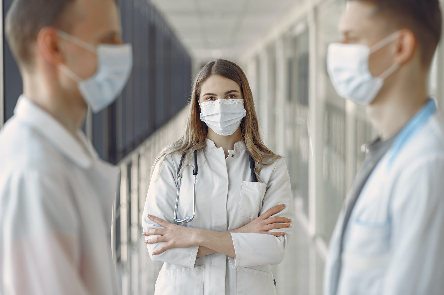 woman in white coat wearing white face mask